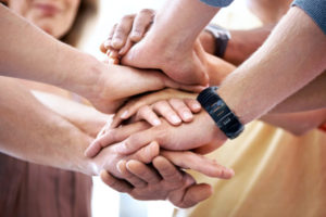A closeup cropped shot of diverse hands stacked on top of each other